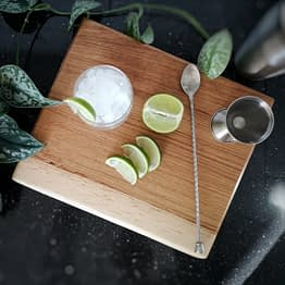solid oak live edge chopping board in kitchen with lime coctail and ice