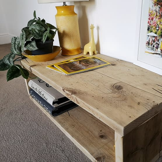 A rustic, handmade coffee table made of reclaimed wood with plants, magazines and yellow lamp