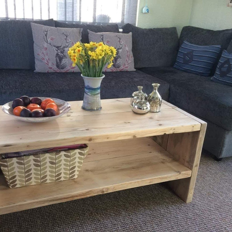 A rustic wooden coffee table with grey sofa