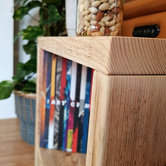 A reclaimed timber side table with pistachios on and a book inside