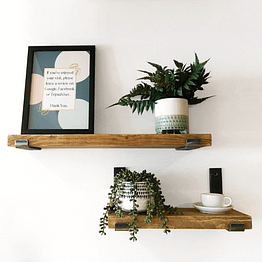 A rustic farmhouse shelves fixed to a wall with photo frame and plants