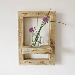 A small reclaimed wood rustic shelf frame with flowers and a glass jar
