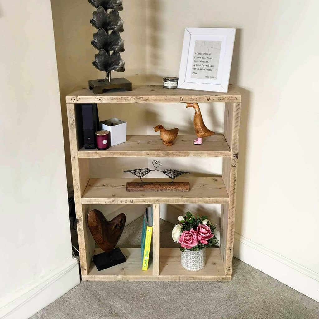 A rustic reclaimed timber bookcase with ornaments on