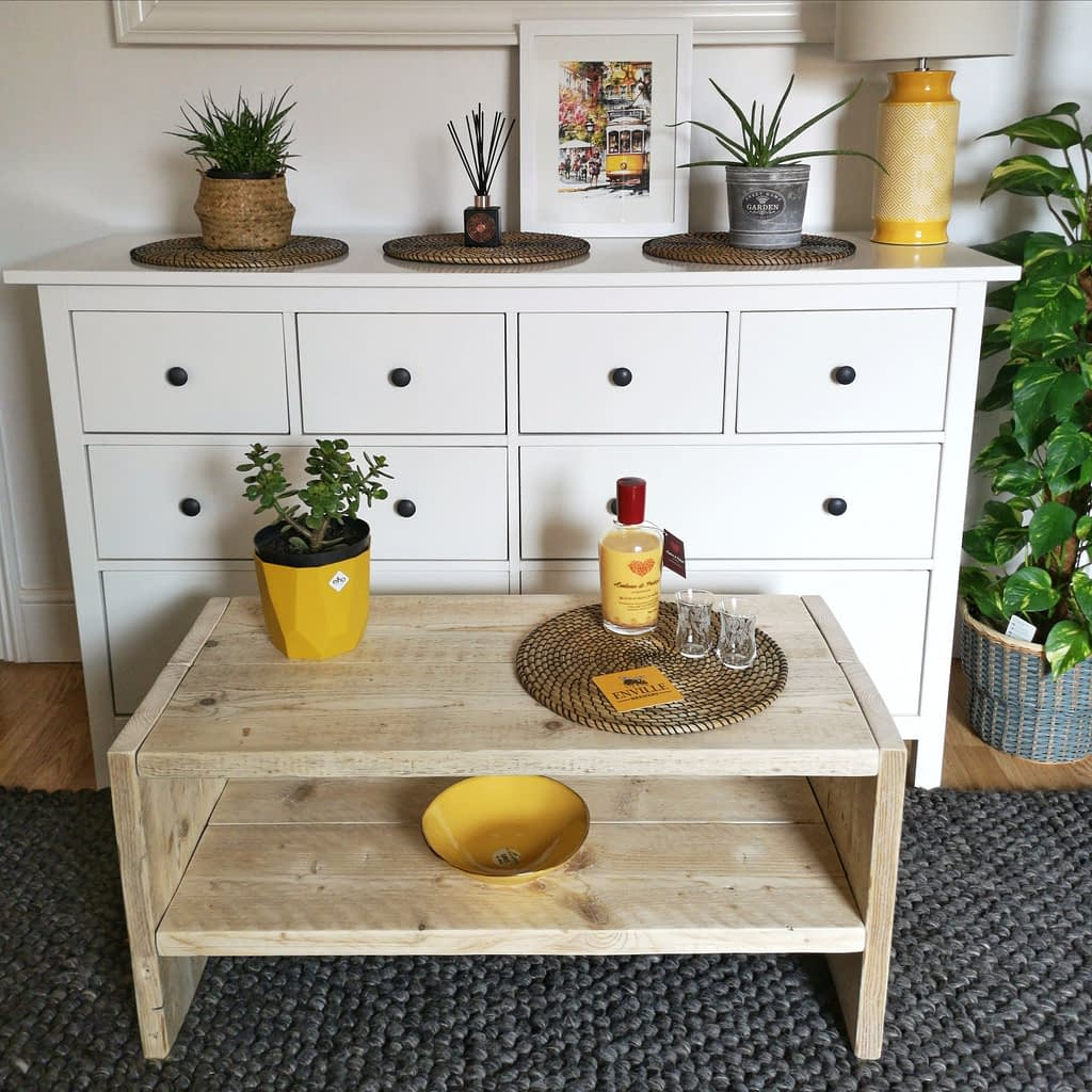 A rustic wood coffee table with liquer and plant