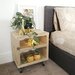 A rustic bedside table with yellow ornaments and green plant